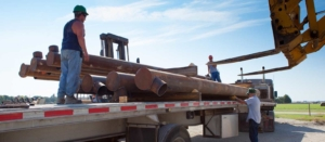 workers unloading large pipes from truck